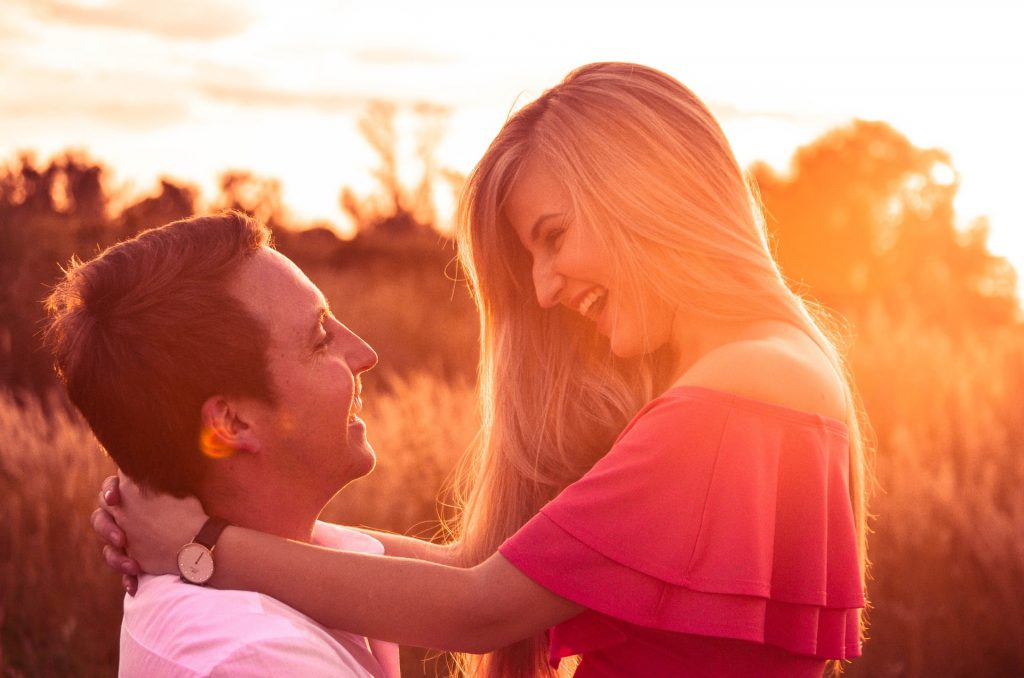 Jeune couple heureux ce regardant en souriant sur fonc de couché de soleil